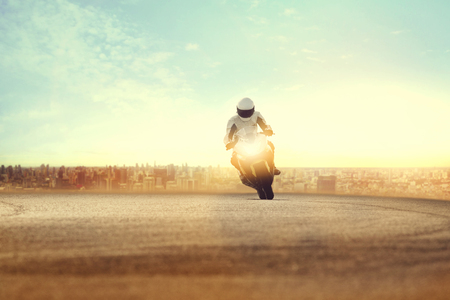 man riding sport motorcycle on dirt road against urban building scene