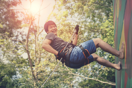 asian younger man hanging on clip hiking safety rope and laughing with happiness emotion