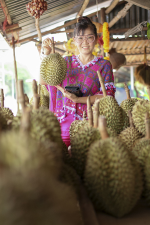 asian woman holding durian fruit and toothy smiling with happiness Stock Photo