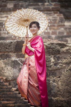 thai woman wearing period tradition clothes style toothy smiling face in ayutthaya heritage place