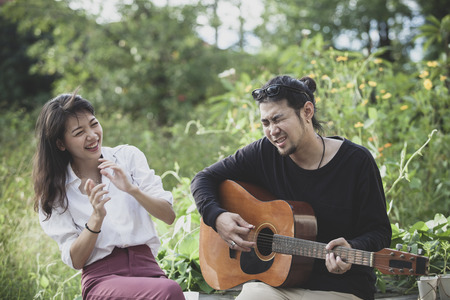 asian younger man and woman playing guitar with happiness emotion