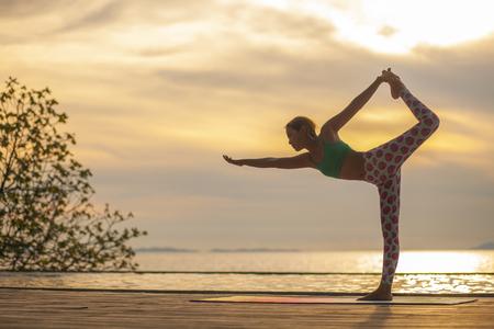 woman playing yoga on sea side
