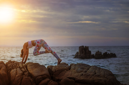 woman playing yoga pose on sea coast against beautiful sun rising sky