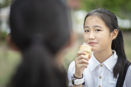 asian teenager eating icecream cone with happiness face Stockfoto