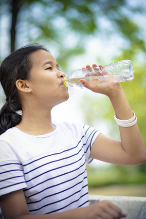 asian teenager drinking water from plastic bottle