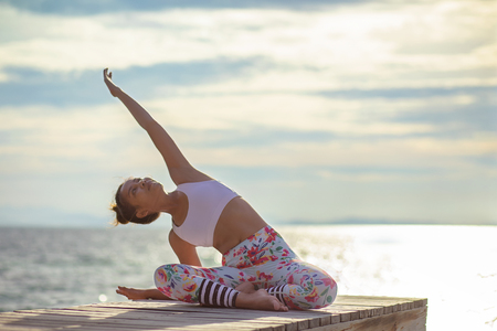younger woman playing yoga pose on sea pier
