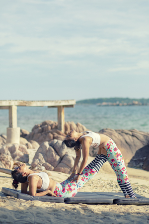 two asian woman playing yoga pose on sea beach