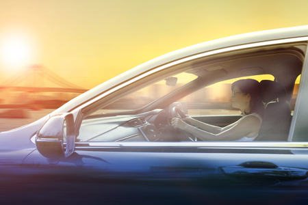younger woman driving passenger car in urban against sunset sky city Stock Photo