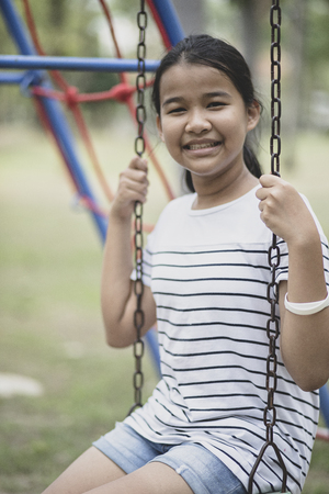 asian teenager sitting on swing in public park toothy smiling face happiness emotion