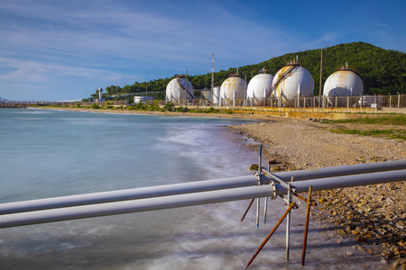 sea coast and gas storage tank in heavy petrochemical industry estate