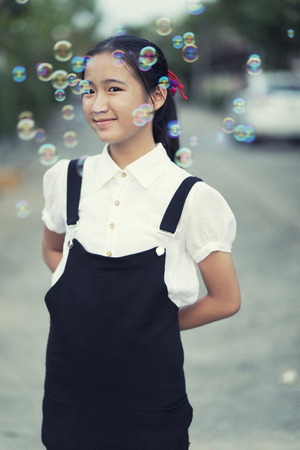 asian teenager smiling face relaxing outdoor with soap bubble floating Stockfoto