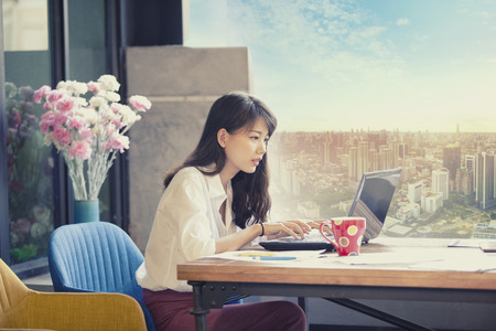 asian freelancer working on computer laptop against urban office building background