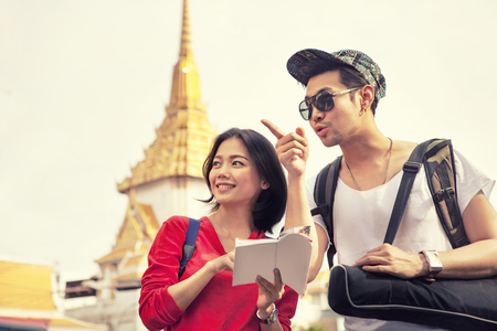 younger asian tourist holding guide book standing in traveling destination in bangkok thailand