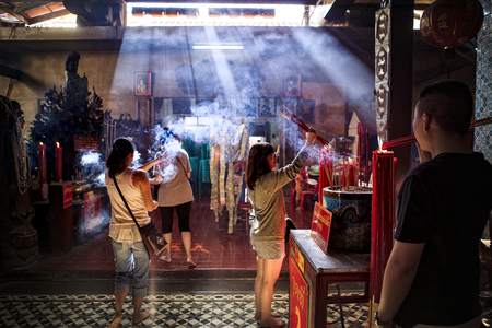 chacheongsao thailand - december14,2014 : unidentified people standing in chinese shrine with smoke of incense chacheongsao province eastern of bangkok