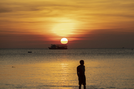 silhouette photography of man at sea beach against beautiful sunset sky background