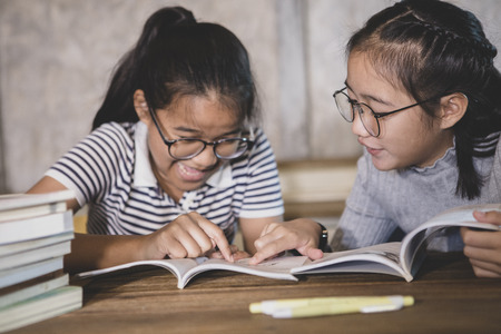 two asian student reading a school book with happiness emotion