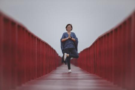 asian woman playing yoga pose on red wooden bridge Фото со стока