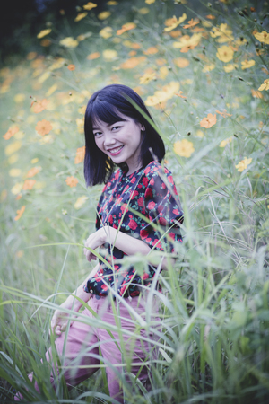 portrait of asian younger woman toothy smiling happiness face in yellow flower field