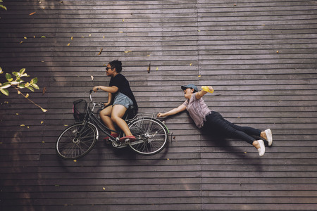 two woman kidding ride on bicycle over wood terrace Stock Photo