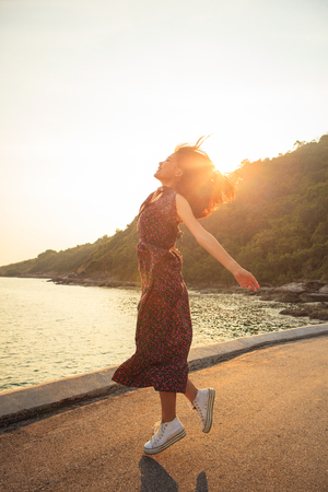 asian younger woman jumping and floating mid air against beautiful sun light Stock Photo