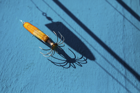 light and shadow of old squid lure on blue wood floor