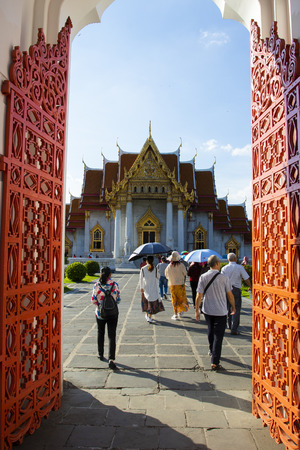 bangkok thailand - october27,2018 : group of tourist walking through wat benchamabophit entry door ,wat ben or marble temple is one of most popular traveling destination in heart of thailand capital