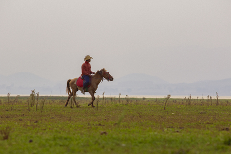 country man riding on horse back