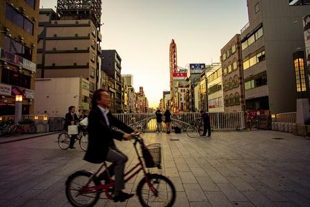 dotonbori osaka japan - november6,2018 unidentified man riding bicycle passing dotonbori bridge ,dotonbori is one of most pupular shopping destination in heart of osaka japan Sajtókép
