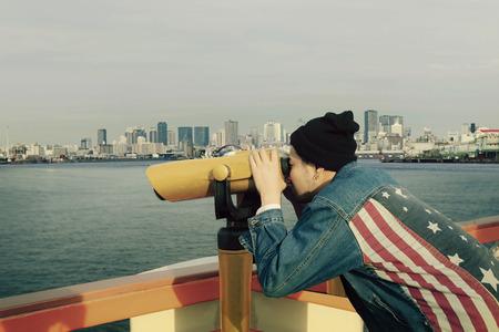 hipster man wearing american flag jeans jacket looking through binocular lens against urban building Stockfoto