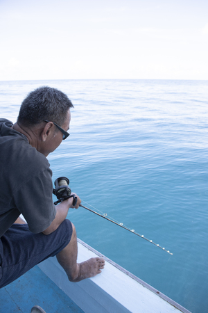 man fishing on boat floating over blue sea water Stok Fotoğraf