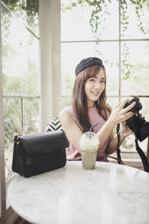 portrait younger asian woman relaxing holding dslr camera in hand Stockfoto