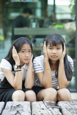 two asian teenager using hand close her ear for not listening any sound