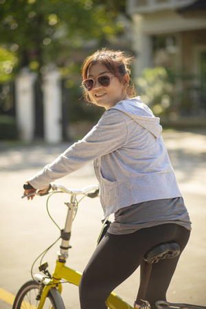 woman wearing sport clothes toothy smiling face on  mini bicycle