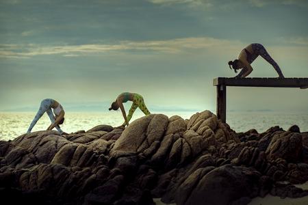 three woman playing yoga pose on sea beach Foto de archivo - 113431718