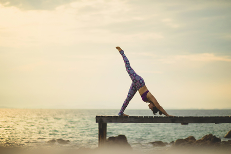 woman playing yoga pose on beach pier with morning light