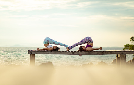couples of woman playing yoga pose on beach pier with moring sun light Reklamní fotografie