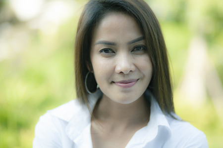 close up face asian younger woman toothy smiling face against green natural background