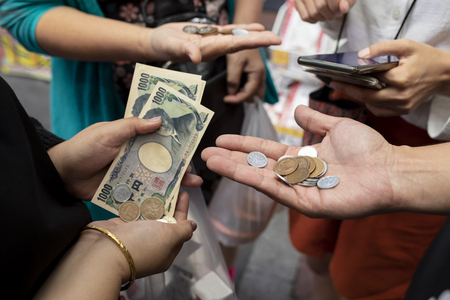 tourist hand and japanese yen banknote in traveling shopping area