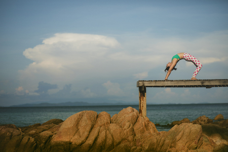 health woman relaxing and playing yoga pose on beach pier