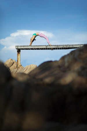 woman relaxing vacation playing yoga pose on beach pier