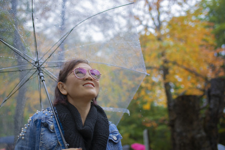 toothy smiling face of woman tourist with rain umbrella standing in autumn color leaves in hokkaido japan ,hokkaido is most popular autumn season traveling destination in japan Stock Photo