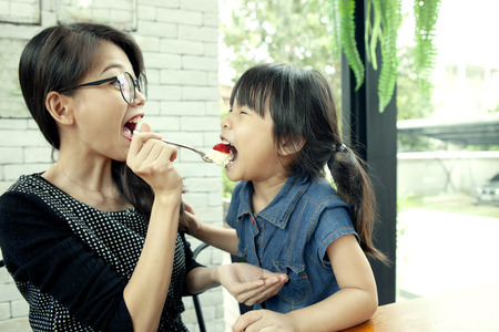 asian woman and daughter eating strawberry cake in home living room