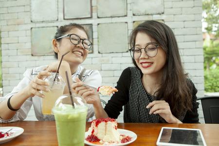 Deux femmes asiatiques bonheur émotion mangeant un gâteau au fromage aux fraises au café