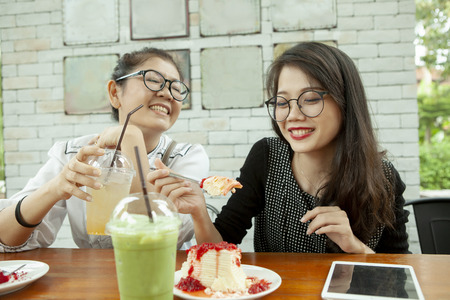 two asian woman happiness emotion eating strawberry cheese cake in cafe Stockfoto - 113429327