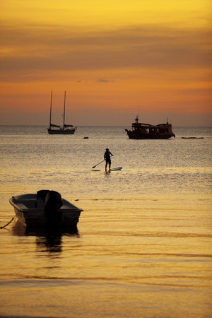 man standing on sup ,stand up paddle board sailing in koh tao harbor against beautiful sunset sky 版權商用圖片