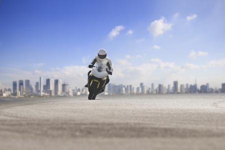 man riding big motorcycle on asphalt highway against urban skyline background