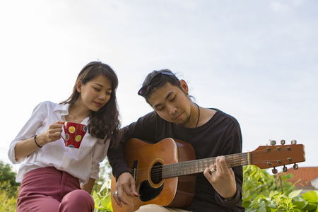 couples of younger asian man and woman relaxing playing guitar in park