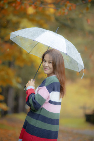 asian younger woman with rain umbrella happiness smiling face stainding in japan autumn park