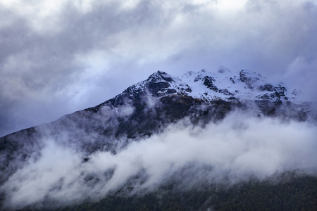 cloud and ice on peak of rock mountain in arthurs pass national park new zealand