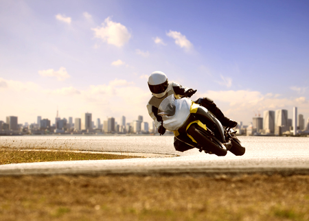 man wearing safety suit riding sport racing motorcycle on sharp curve highway